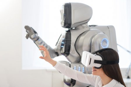 Photo for Touch the world.    Pleasant  beautiful content woman holding hand in front of her  and using virtual reality device while robot standing nearby - Royalty Free Image