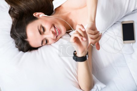 Cheerful delighted  woman resting in bed
