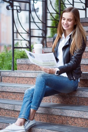 Photo for My lifestyle.  Happy and cheerful young woman reading some articles in a newspaper and drinking coffee while sitting on the stairs - Royalty Free Image