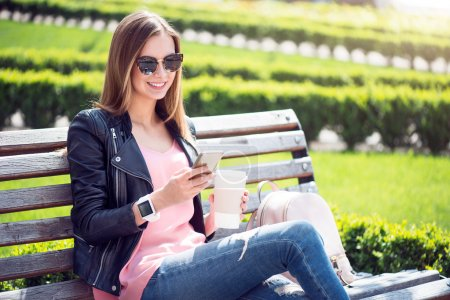 Photo for Happy day. Positive and cheerful young woman using a mobile phone while sitting on a bench in a park and drinking coffee - Royalty Free Image
