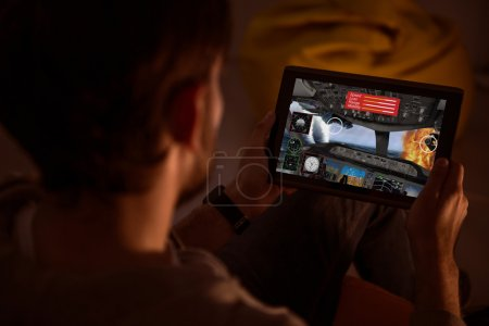 Photo for Some fun. Top view of a man holding a tablet and playing a videogame during the nighttime - Royalty Free Image