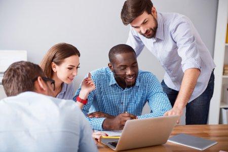 Foto de Echa un vistazo. Colegas profesionales sonrientes positivas usando laptop y discutir proyecto mientras trabajaba en la oficina juntos - Imagen libre de derechos