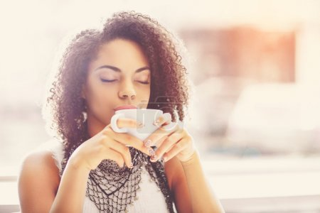 Photo pour Félicité. Jeune femme rêveuse et heureuse retenant une tasse de thé chaud tout en détendant avec des yeux fermés - image libre de droit