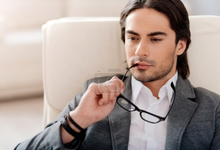 Photo for Mull it over. Concentrated handsome man sitting in the chair and holding his glasses while being involved in thoughts - Royalty Free Image