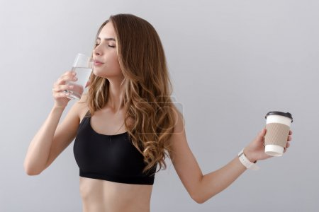 Positive delighted woman drinking water