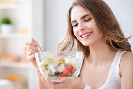 Nice joyful woman eating salad