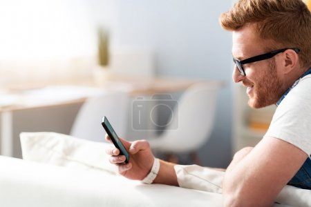 Photo for Digital world. Positive handsome smiling man using cell phone and sitting on the couch while resting at home - Royalty Free Image