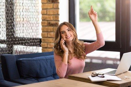 Photo pour Viens me voir. Positif ravi femme souriante assise à la table et appelant serveur tout en parlant sur téléphone portable - image libre de droit