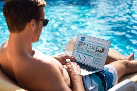 Photo pour Cherchez des informations. Délicieux homme agréable allongé sur le transat et utilisant un ordinateur portable tout en se relaxant près de la piscine - image libre de droit