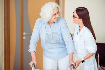 Photo pour Mes soins. Professionnel jeune médecin joyeux aidant vieille femme souriante avec cadre de marche - image libre de droit