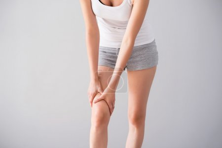 Young woman having knee ache