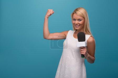 Photo pour Portrait à mi-longueur d'une jolie présentatrice de télévision aux cheveux blonds souriante portant une jolie robe blanche tenant un microphone nous montrant sa force. Isolé sur fond bleu - image libre de droit