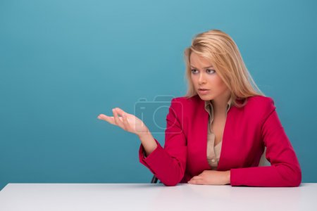 Photo pour Portrait demi-longueur d'une jolie présentatrice de télévision aux cheveux blonds portant une grande veste rouge et une chemise de couleur crème assise à la table parlant avec quelqu'un. Isolé sur fond bleu - image libre de droit