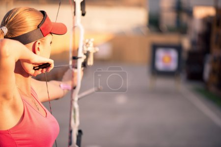 Photo for Selective focus on the lovely young fair-haired woman wearing pink T-shirt and black skirt pulling the bowstring. The target on background - Royalty Free Image