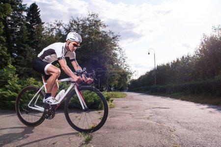 Photo for Full-length portrait of the man wearing sport uniform and sunglasses riding a great bike in the park preparing for the competition - Royalty Free Image