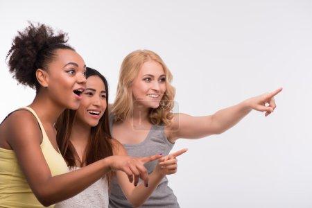 Photo pour Portrait à mi-longueur de trois jeunes jolies filles portant un T-shirt coloré regardant et pointant quelqu'un avec surprise. Isolé sur fond blanc - image libre de droit