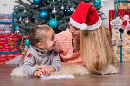 Photo pour Focus sélectif sur la maman aux cheveux blonds souriante portant une casquette rouge couchée sur le sol près du sapin de Noël avec sa petite fille mignonne écrivant une lettre pour le Père Noël - image libre de droit