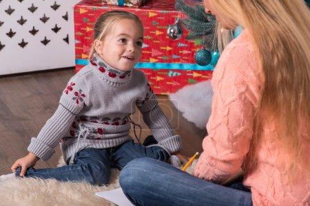 Photo pour Maman et fille portant de jolis pulls chauds et un jean assis sur le sol près du sapin de Noël parlant et écrivant une lettre pour le Père Noël - image libre de droit