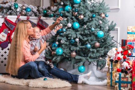 Photo pour Portrait demi-longueur de la petite fille souriante blonde mignonne avec sa jolie maman portant des chandails chauds et jeans, assis côté près de l'arbre de Noël décorant - image libre de droit