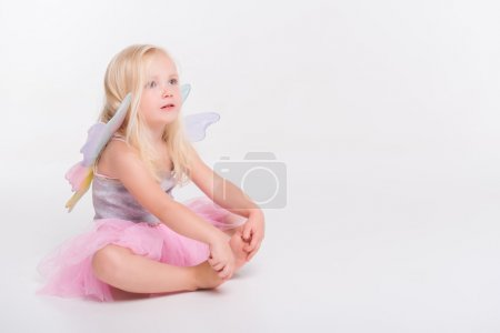 Photo pour Full-length portrait of little fair-haired lovely thoughtful girl wearing pretty grey vest and pink skirt sitting aside looking at something. Isolated on white background - image libre de droit