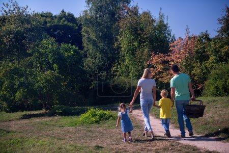 Photo pour Portrait complet d'une jeune famille heureuse revenant du pique-nique tenant un panier en osier - image libre de droit