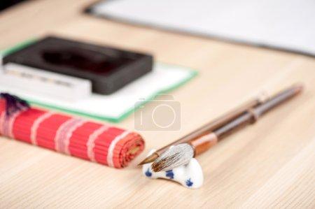 Photo pour Pratique de calligraphie. Image rapprochée de l'ensemble pour calligraphie japonaise ou chinoise avec pinceau et encre disposés sur une table en bois - image libre de droit