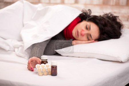Frustrated woman lying in bed with pills