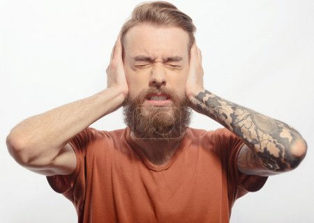 Photo pour Too loud. Young bearded man covering his ears with two palms with his eyes closed while standing against white background with copy space - image libre de droit