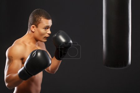 Photo pour Warming up before the fight. Confident young African boxer in sports gloves training with a punch bag isolated on black background - image libre de droit