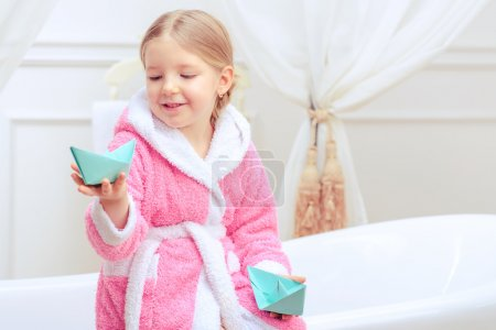 Photo pour Bath time is fun. Closeup image of a cute little girl in a pink bathrobe holding paper ships while sitting on a luxurious bathtub with happy face expression - image libre de droit