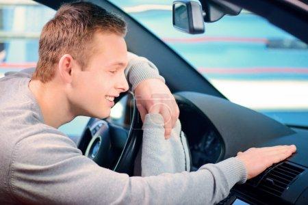 Photo pour Il nettoie sa voiture. Vue latérale d'un beau jeune homme souriant nettoyant son tableau de bord de voiture avec un essuie-glace et touchant avec expression de visage heureux - image libre de droit