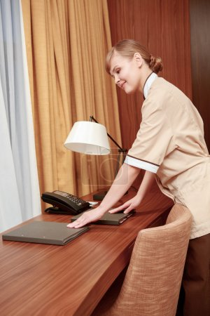 Maid arranging hotel stationery