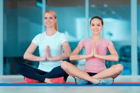 Photo pour Trouver la paix intérieure et l'harmonie. Belle adolescente et sa mère dans le yoga de formation de vêtements de sport et prenant des positions semblables sur le tapis dans le club sportif - image libre de droit