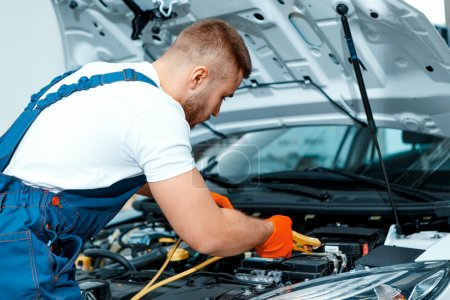 Photo for Passionate about cars. Handsome muscular car mechanic in uniform checking the engine in car service station - Royalty Free Image