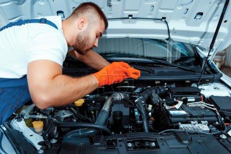 Photo pour Meilleur mécanicien du coin. Beau mécanicien de voiture musculaire en uniforme vérifiant le moteur dans la station-service de voiture - image libre de droit