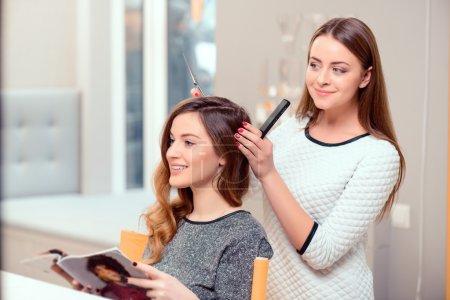 Photo pour Je vais changer de style. Jeune belle femme discutant de coiffure avec son coiffeur tenant un peigne et des ciseaux tout en étant assis dans le salon de coiffure - image libre de droit