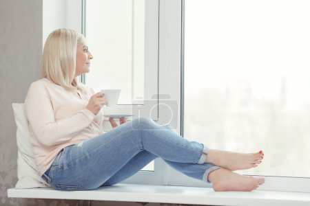Photo for Beautiful view. Attractive middle aged woman sitting on the windowsill and looking out of the window - Royalty Free Image