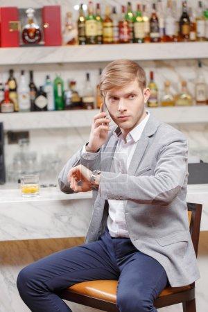 Photo pour Anticipant une réunion. Jeune homme en chemise et veste de parler au téléphone et en regardant sa montre en étant assis au comptoir du bar - image libre de droit