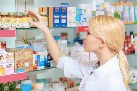 Pharmacist arranging medicines on the shelves