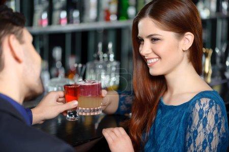 Photo pour Un toast pour l'amour. Gros plan d'une jeune femme brune souriante trinquant avec un cocktail en compagnie d'un jeune homme - image libre de droit