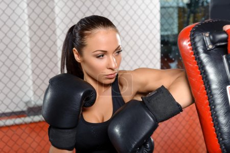 Photo for Striking a punching pad. Close-up of a young beautiful fighter punching a pad in a boxing ring - Royalty Free Image