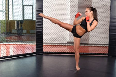 Photo for High kick. Strong sportswoman shows her high kick in a boxing ring - Royalty Free Image