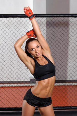 Female kickboxer poses at a ring