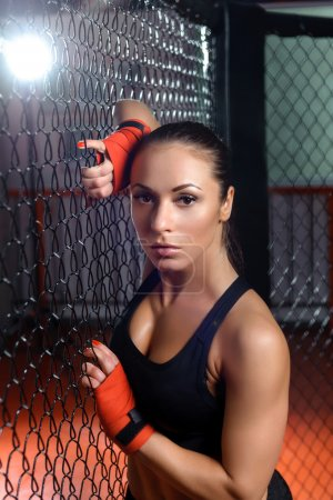 Photo for Pure seduction. Young fit attractive sports woman with boxing bandages on her hands hanging on a fighting cage in a gym - Royalty Free Image