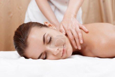 Photo pour Un corps sain. Gros plan des mains féminines donnant massage à l'huile à une jeune brune dans un salon de spa - image libre de droit