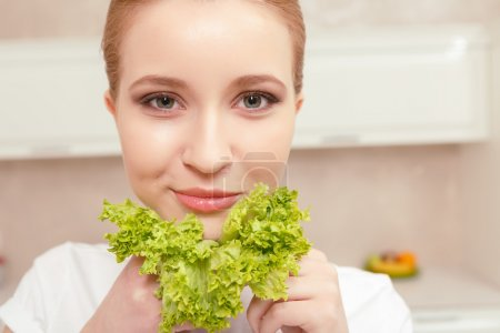 Lady smiles while holding lettuce