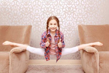 Little flexible girl splitting legs apart