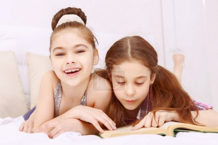 Photo for To each his own. Two joyful little girls lying and  reading book very attentive - Royalty Free Image