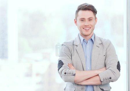 Photo pour Reste positif. Portrait de jeune homme d'affaires souriant debout devant la fenêtre et pliant les bras - image libre de droit