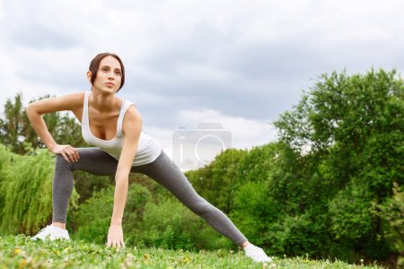 Beautiful young girl doing gymnastic in park